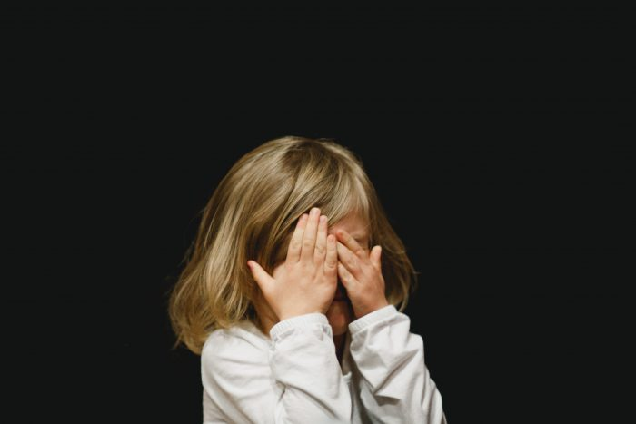 Girl covering her face with both hands. Credit: Unsplash