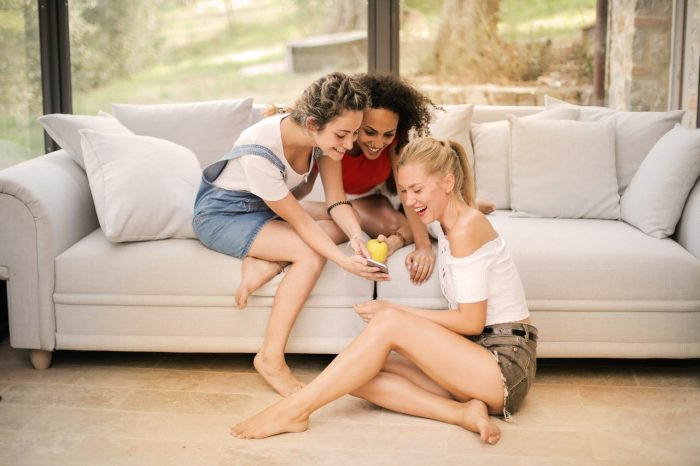 happy-diverse-friends-laughing-with-smartphone-at-home